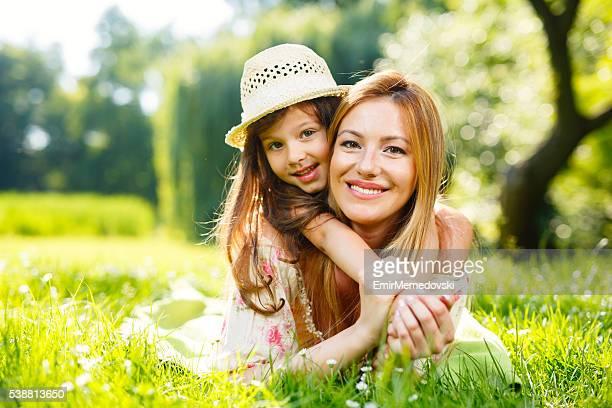 Mutter und Tochter spielen auf dem Rasen im park.