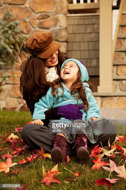 Mother and daughter playing outdoors in autumn