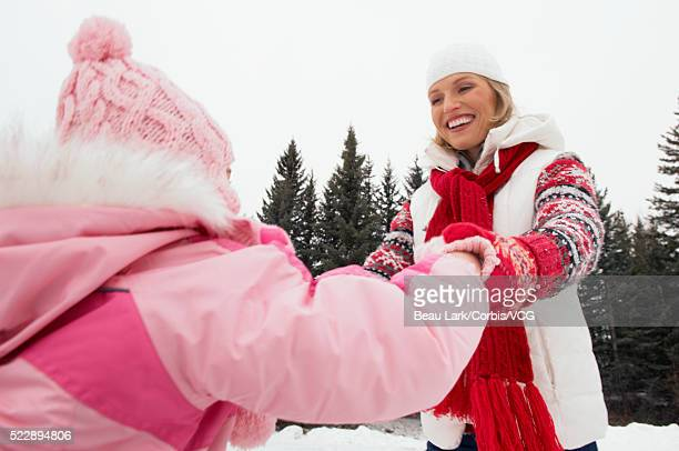 Mother and daughter playing outdoors in winter