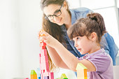 Young mother and cute girl playing together at home with colorful toy wood blocks, education and fun concept