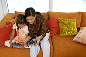 Mother and daughter (8-10) playing video game, elevated view