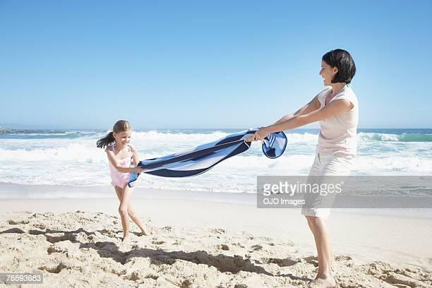 Una madre e hija jugando con una toalla de playa