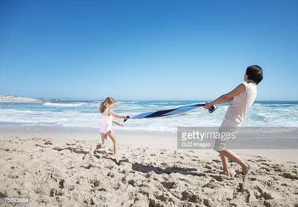 A mother and daughter playing with a beach towel