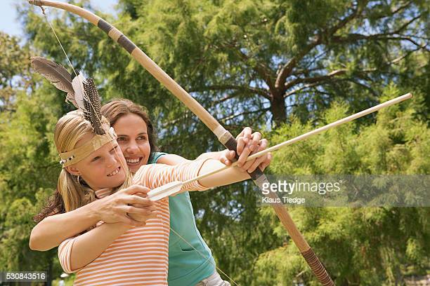 Mother and daughter playing with a bow and arrow