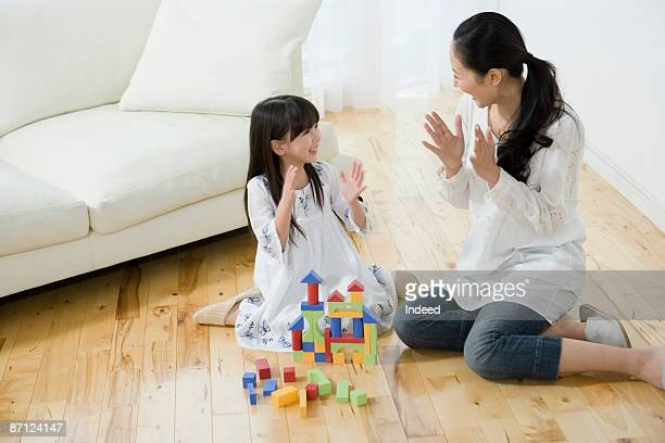 Mother and daughter playing with hands
