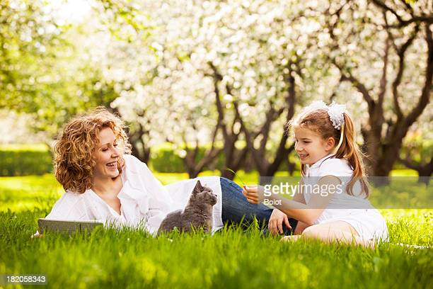Mother and daughter playing with kitten on lawn in park