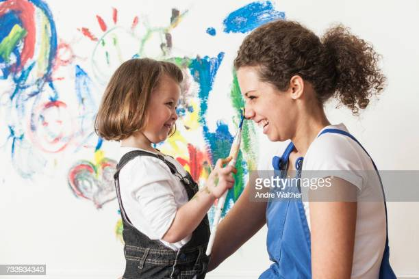 Mother and daughter playing with paint