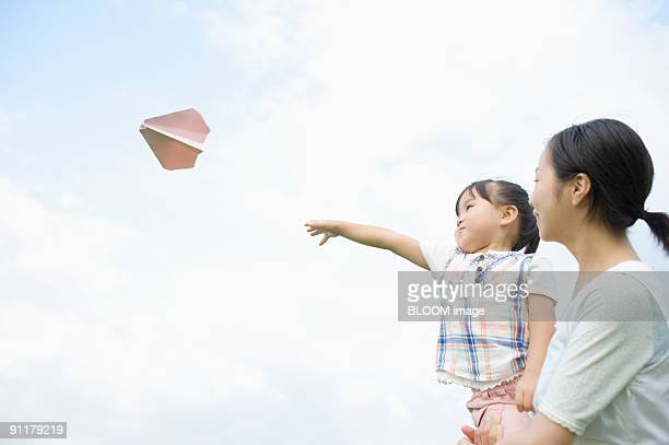 Mother and daughter playing with paper airplane