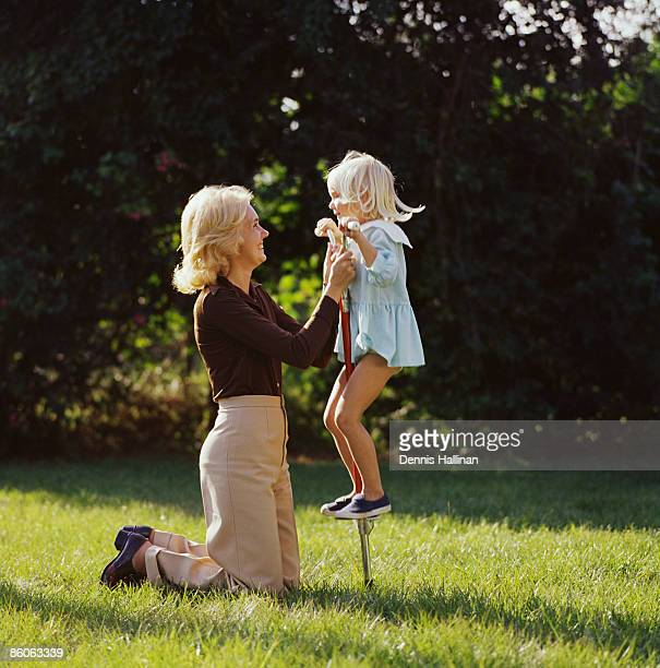 Mother and daughter playing with pogo stick