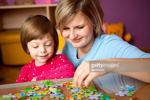 Mother and daughter playing with puzzle