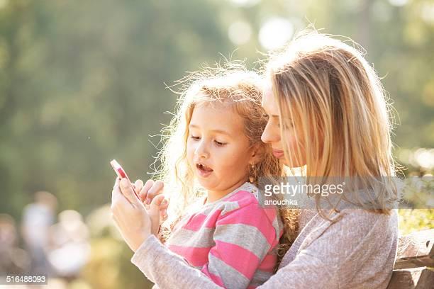 Mutter und Tochter spielen mit smartphone im Freien