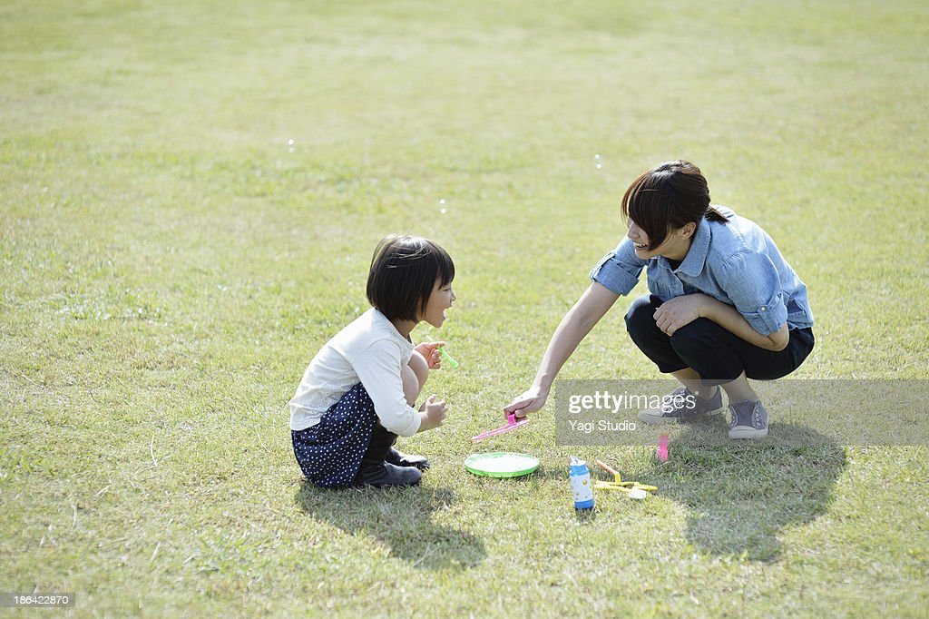 Mother and daughter playing with soap bubbles : Stock Photo