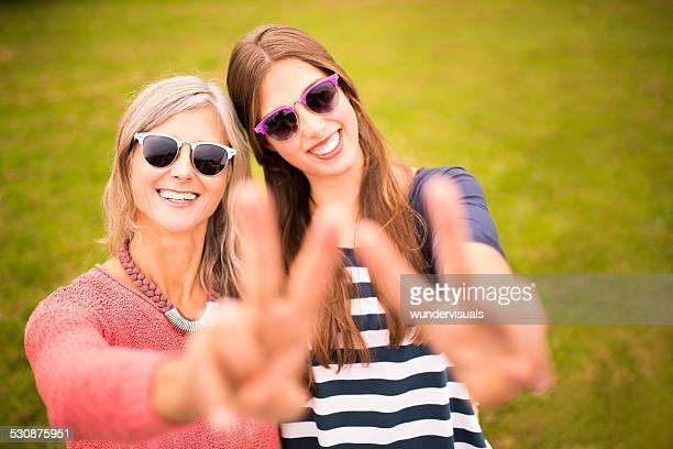 Mãe e filha com Pose engraçadas Sunnies para uma foto