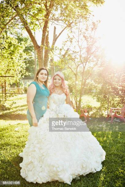 Mother and daughter posing for quinceanera photos in backyard