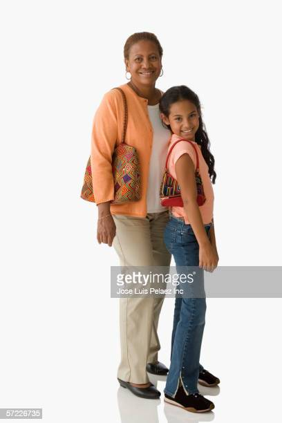 Mother and daughter posing for the camera with purses