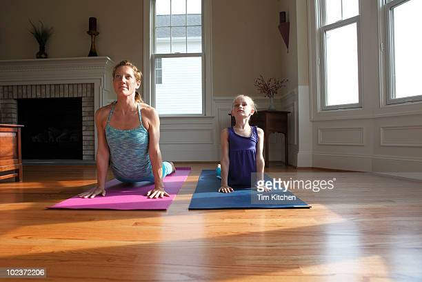 Mother and daughter practicing yoga in home
