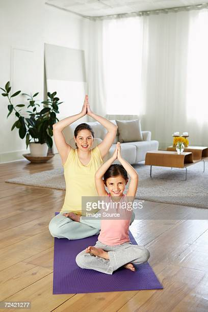 Mother and daughter practising yoga