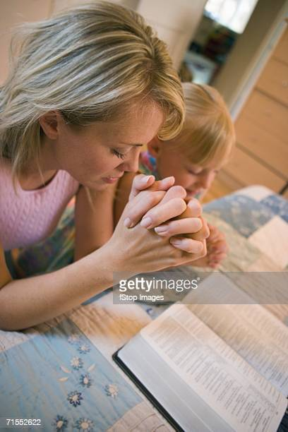 Mother and daughter praying together in front of an open bible