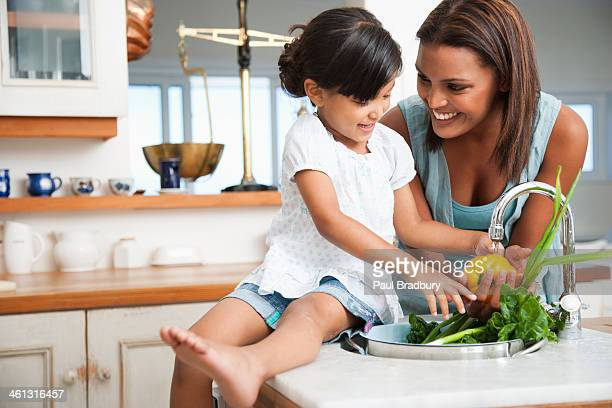Mother and daughter preparing a meal in kitchen