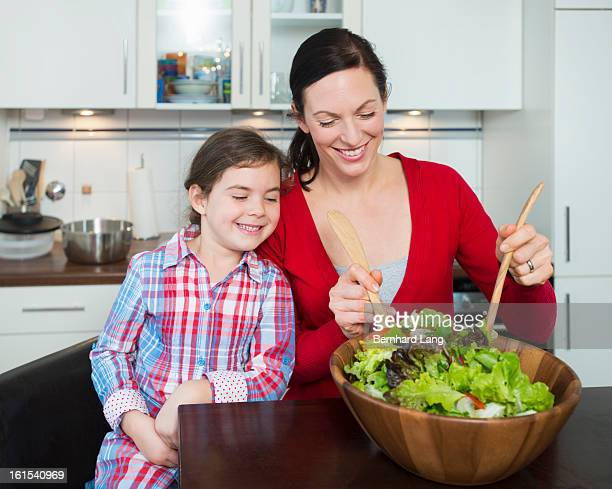 Mother and daughter preparing a salad in a kitchen