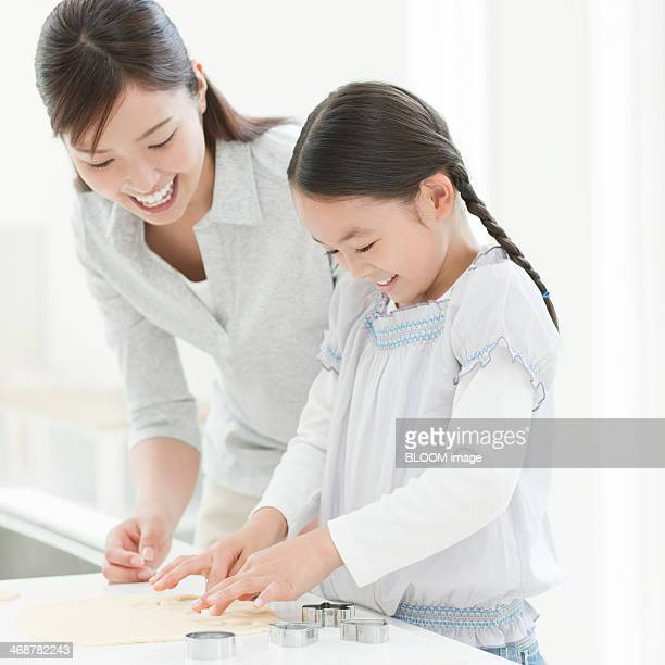 Mother And Daughter Preparing Cookie