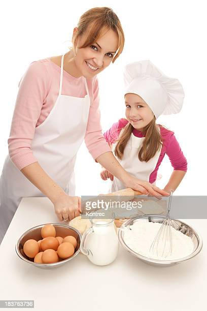 Mother and daughter preparing dough for various pastry products