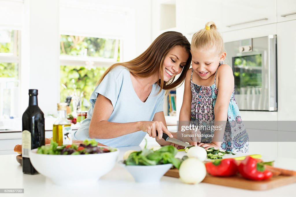 Mother and daughter (4-5) preparing food in kitchen : Stock Photo
