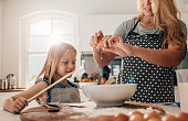 Mother cracking an egg into bowl with her daughter in kitchen. Woman and little girl preparing food in kitchen.