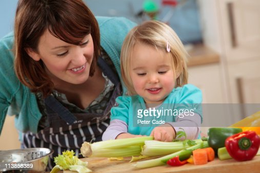 mother and daughter preparing food : Stock Photo