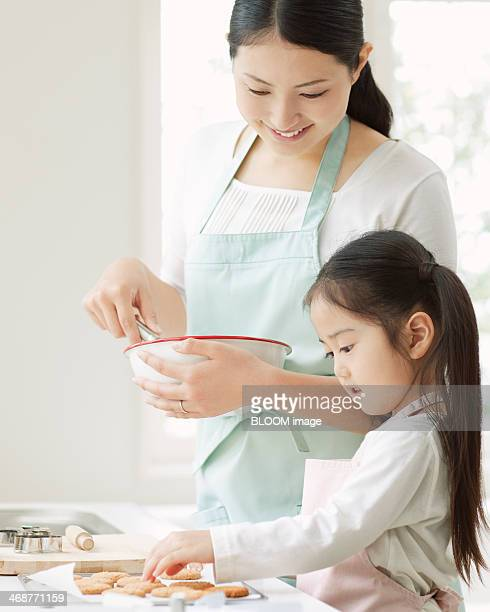 Mother And Daughter Preparing Food