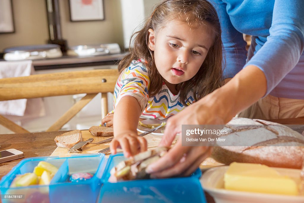 Mother and daughter preparing lunchbox for school.