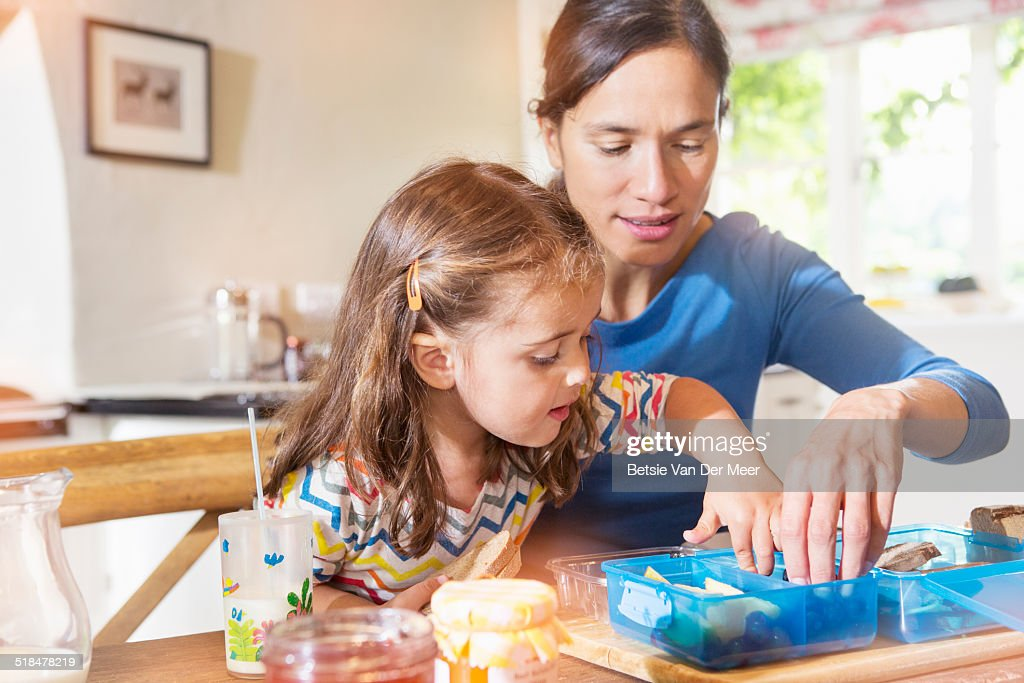 mother and daughter preparing lunchbox for school