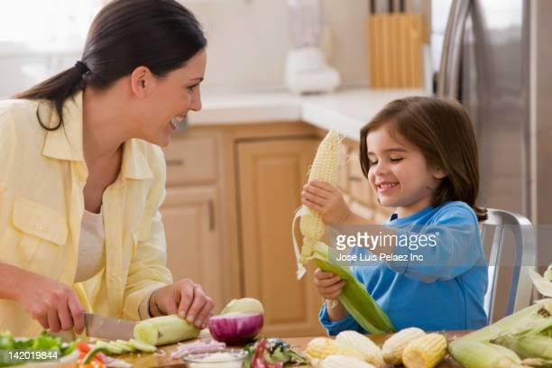 Mother and daughter preparing meal together
