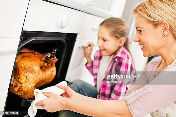 Mother and daughter preparing turkey for Thanksgiving day.