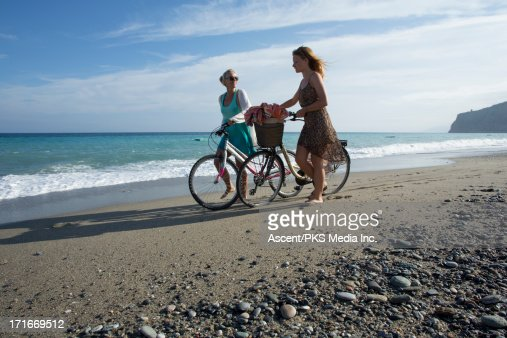 Mother and daughter push bukes along beach edge : Stock Photo