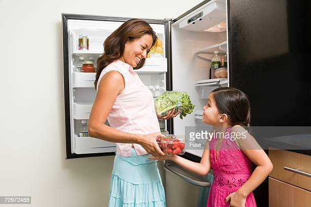 Mother and daughter putting away groceries