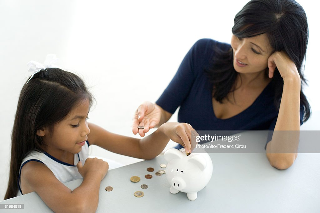 Mother and daughter putting coins in piggy bank together, high angle view : Stock Photo