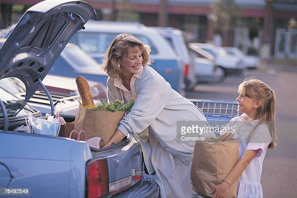 Mother and daughter putting groceries in car