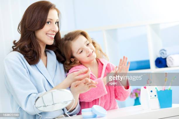 Mother and daughter putting on hand cream moisturizer