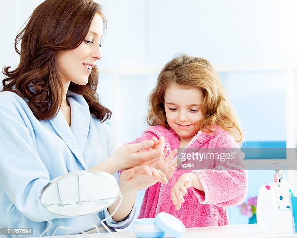 母と娘のハンドクリームの保湿剤をつけて