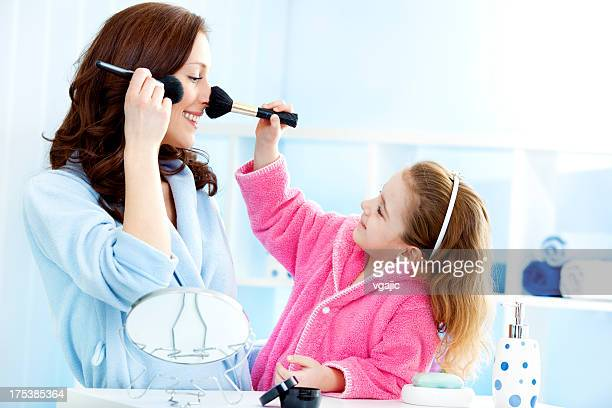 Mother and daughter putting on make up.