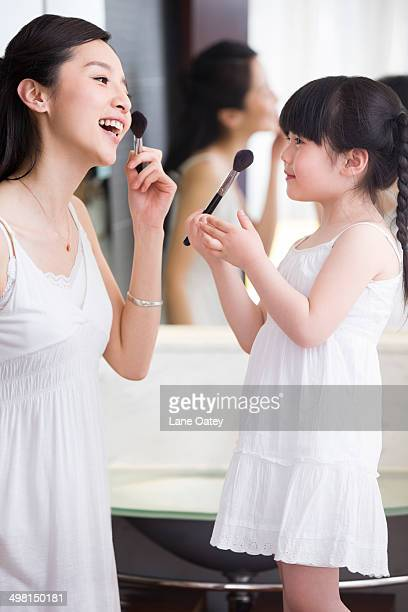 Mother and daughter putting on makeup