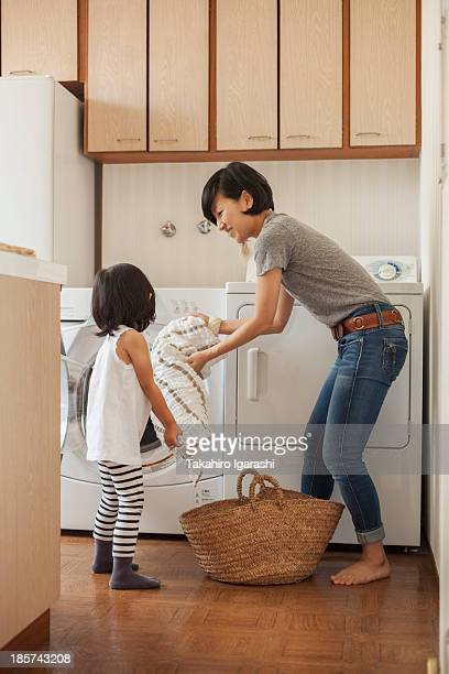 Mother and daughter putting towel into washing machine