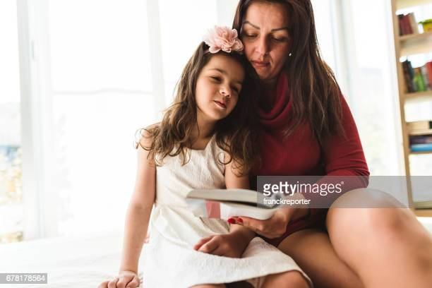 mother and daughter read a book together