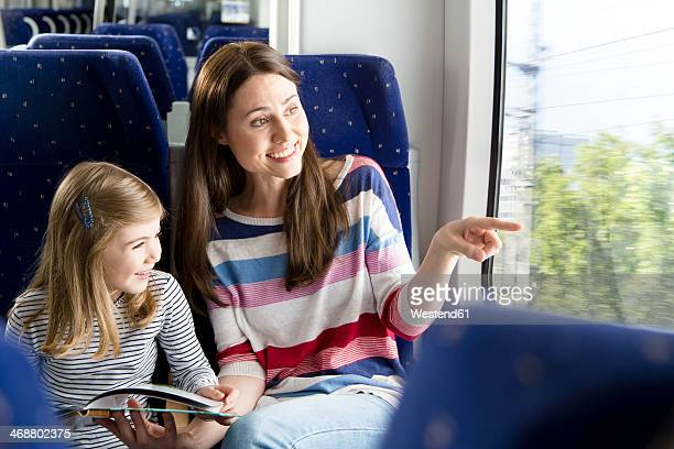 Mother and daughter reading book in a train