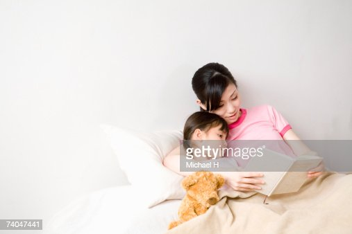 Mother and daughter (6-7) reading book in bed