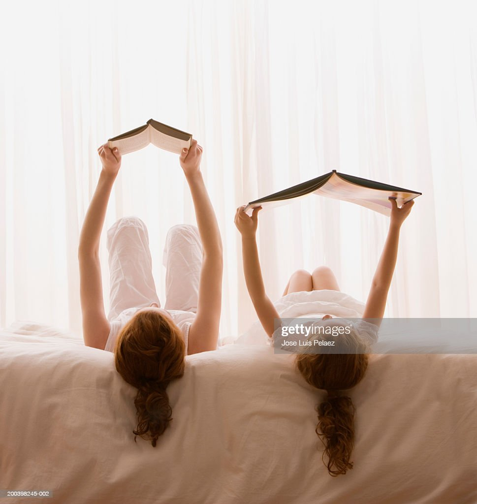 Mother and daughter (4-6) reading book in bed, rear view