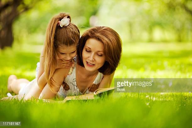 Mère et fille lire livre dans le parc