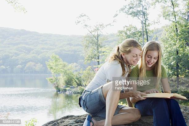 Mother and daughter reading book together while camping in nature