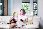 Mother and Daughter reading magical book in living room